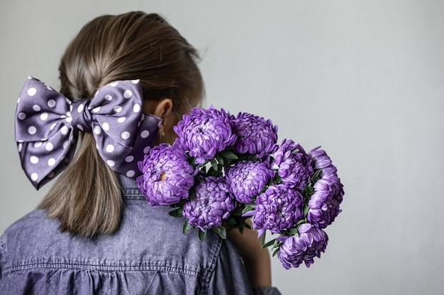 Menina com um lindo laço no cabelo segura um buquê de crisântemos azuis, vista traseira.