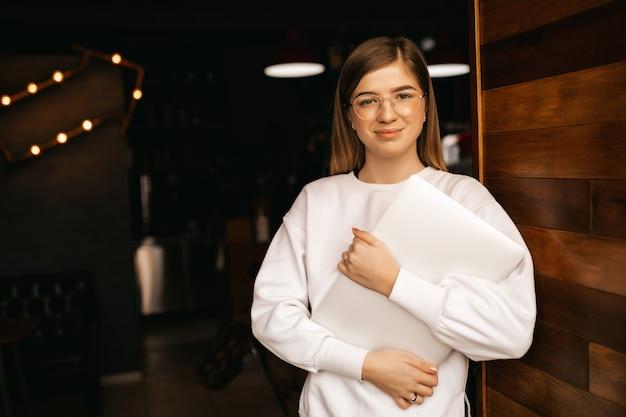 Menina com um lindo sorriso segurando um laptop nas mãos