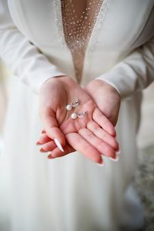Menina com um lindo vestido branco segurando brincos nas mãos