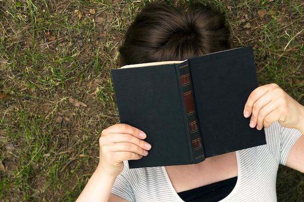 Menina com um livro encontra-se na grama, vista superior