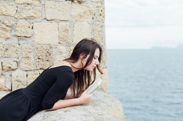 Menina com um livro perto do mar