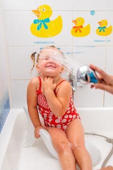 Menina com um maiô vermelho tomando banho