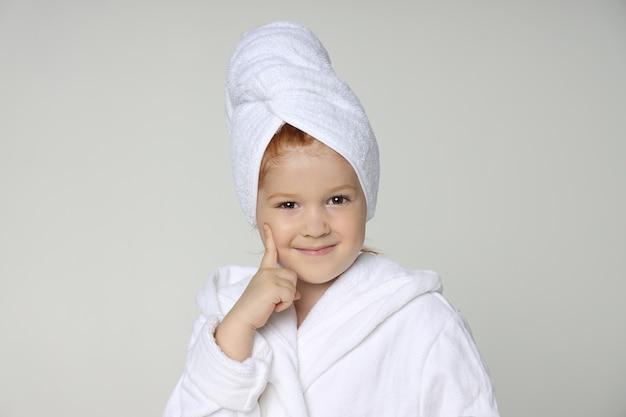 Menina com um manto branco e uma toalha na cabeça depois do banho e lavando o cabelo. cosméticos infantis e cuidados com a pele, tratamentos de spa