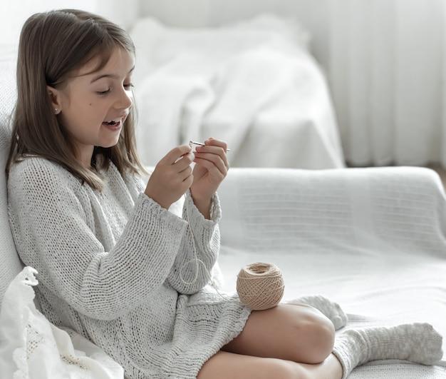 Menina com um novelo de linha e uma agulha em casa no sofá.