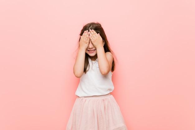 Menina com um olhar de princesa cobre os olhos com as mãos, sorri amplamente esperando por uma surpresa.