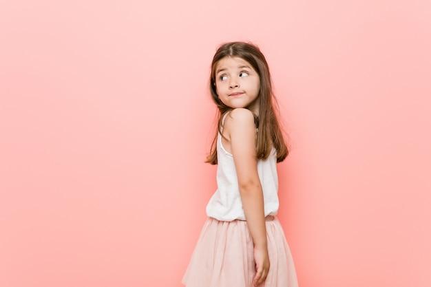 Menina com um olhar de princesa parece de lado sorridente, alegre e agradável.