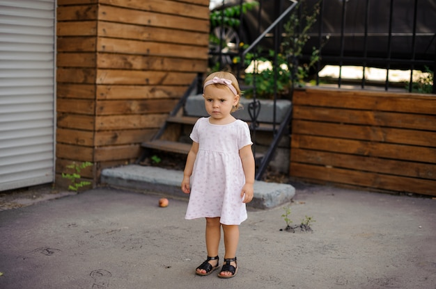 Menina com um olhar sério, vestido com um lindo vestido rosa