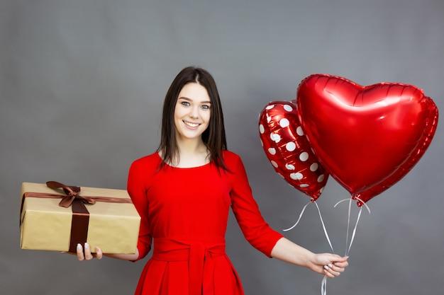 Menina com um presente e balões. garota recebendo uma caixa de presente e balões em forma de coração para dia dos namorados.