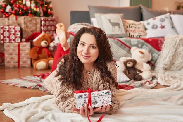 Menina com um presente em casa no interior do ano novo