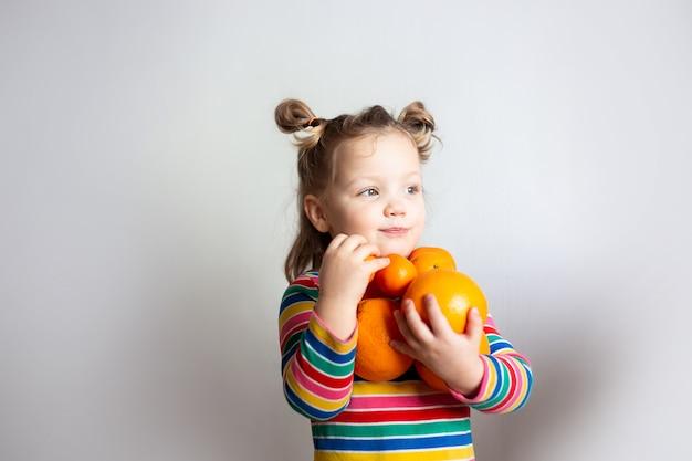 Menina com um rabo de cavalo em uma jaqueta listrada colorida com um grande número de laranjas