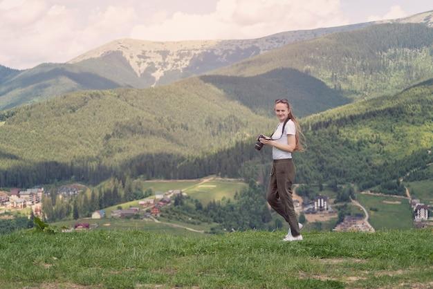 Menina com um rosto descontente e pé de câmera em um fundo de montanhas. floresta no fundo