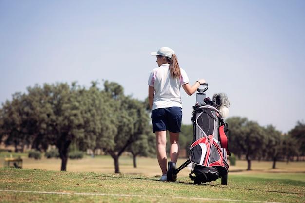 Menina com um saco de tacos de golfe, olhando para o horizonte