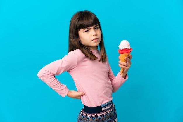Menina com um sorvete de corneta isolada em um fundo azul sofrendo de dor nas costas por ter feito um esforço