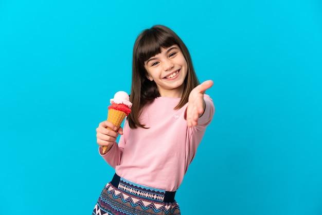 Menina com um sorvete de corneta isolado na parede azul apertando as mãos para fechar um bom negócio