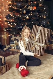 Menina com um suéter branco perto da árvore de natal com presente