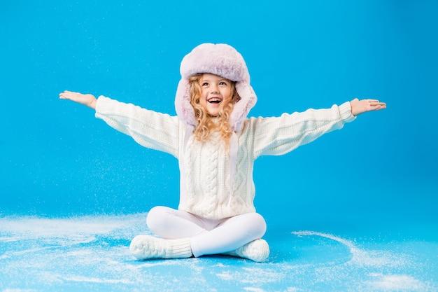 Menina com um suéter branco quente e um chapéu com protetores de orelha sentada sobre um fundo azul