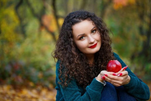 Menina com um suéter verde e uma maçã nas mãos na floresta de outono