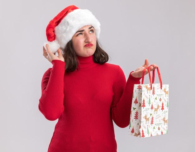 Menina com um suéter vermelho e chapéu de papai noel segurando um saco de papel colorido com presentes de natal olhando para cima com expressão cética em pé sobre fundo branco
