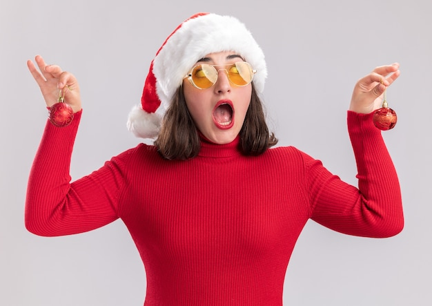 Menina com um suéter vermelho e chapéu de papai noel usando óculos segurando bolas de natal, olhando de lado surpresa em pé sobre um fundo branco