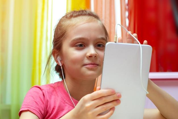 Menina com um tablet. comunicação, treinamento, jogos de criança, adolescente com aparelho moderno. tecnologias sociais interativas no mundo