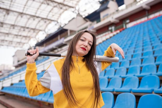 Menina com um taco em um estádio vazio. para qualquer propósito