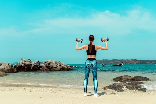 Menina com um treinamento corporal perfeito em uma praia de verão com um halteres. esporte, fitness, exercício e dieta.