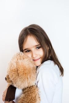 Menina com um urso de peluche favorito, infância e cuidado, família e amigos. menina, tocando, e, abraçando, brinquedo