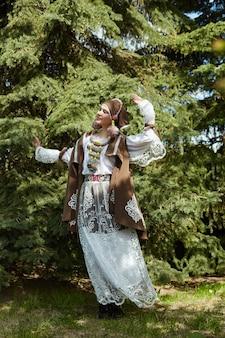 Menina com um vestido artesanal de moda étnica vintage posando ao ar livre.