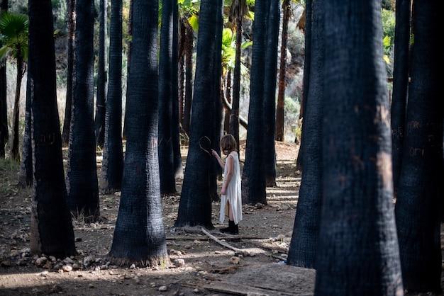 Menina com um vestido branco em uma floresta cercada por vegetação sob a luz do sol
