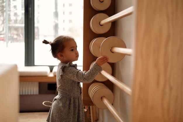 Menina com um vestido cinza brincando com ábaco de madeira na sala das crianças aprendendo a contar de madeira