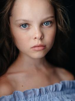 Menina com um vestido de verão em uma visão recortada retrato close-up de parede escura.
