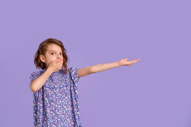Menina com um vestido estampado de flores na boca roxa com a mão em forma de cone chocado