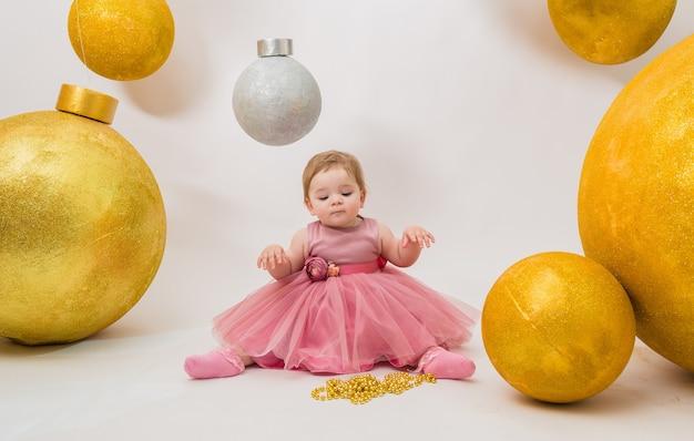 Menina com um vestido tutu rosa com enormes balões festivos em uma parede branca