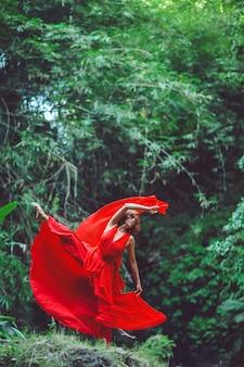 Menina com um vestido vermelho dançando em uma cachoeira.