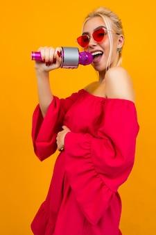 Menina com um vestido vermelho elegante com ombros nus e óculos retrô segurando um microfone e canta