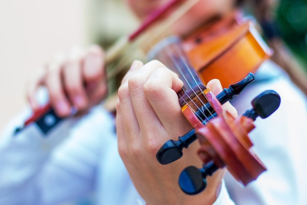 Menina com um violino em um borrão brilhante do bokeh