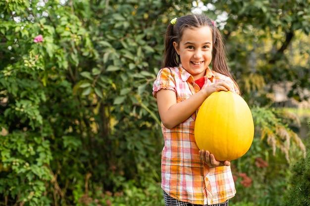 Menina com uma abóbora no jardim