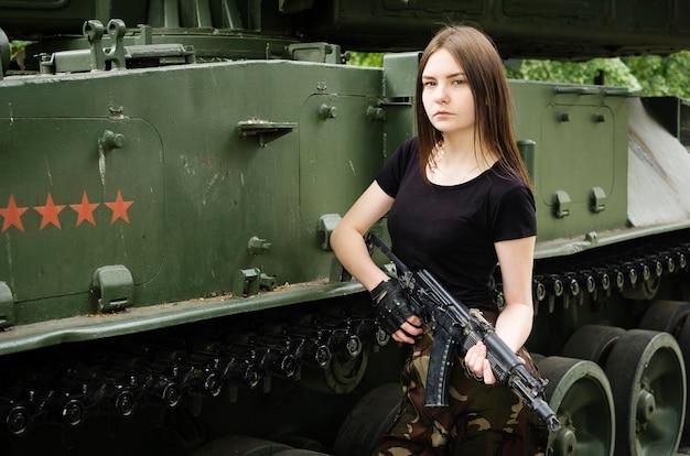Menina com uma arma perto dos veículos blindados