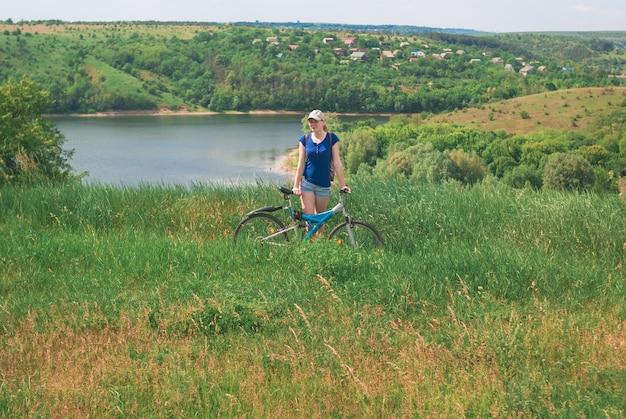 Menina com uma bicicleta na margem do rio.