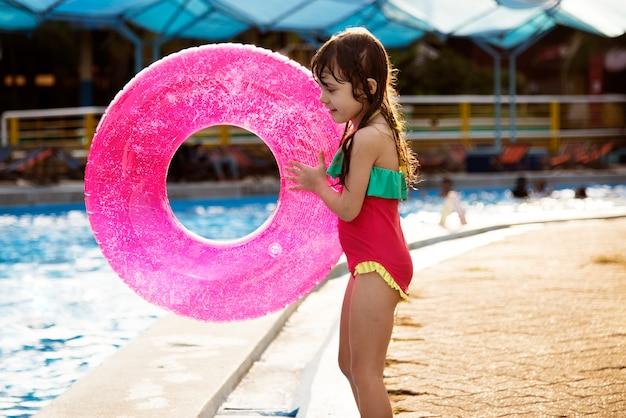 Menina com uma bóia de verão à beira da piscina