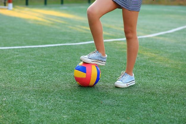 Menina com uma bola nas mãos no campo de futebol.
