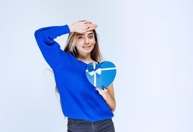 Menina com uma caixa de presente azul parece cansada.