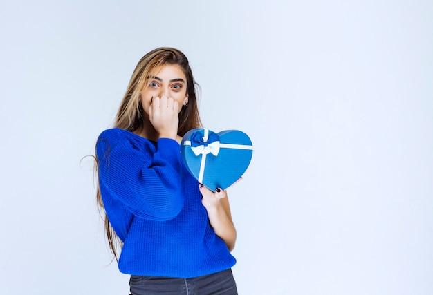 Menina com uma caixa de presente azul parece confusa e surpresa.