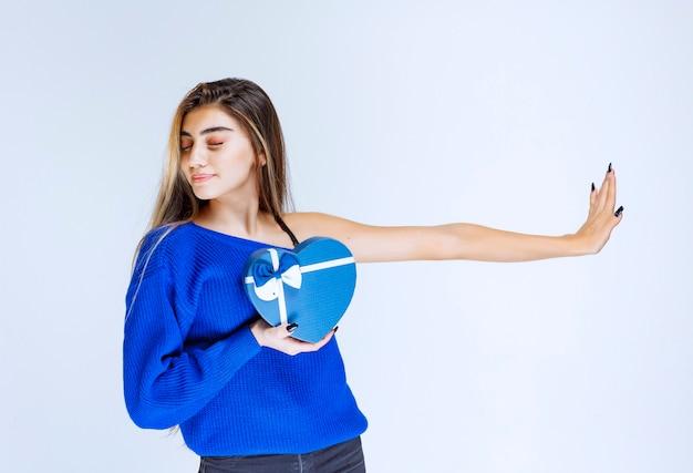 Menina com uma caixa de presente de forma de coração azul, parando os outros.