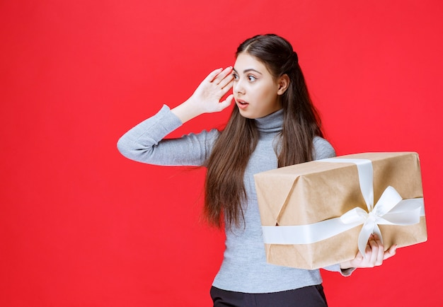 Menina com uma caixa de presente de papelão parece apavorada e cansada.
