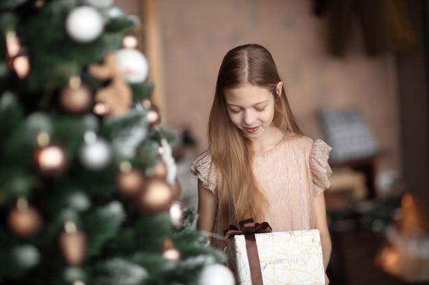 Menina com uma caixa de presente em pé perto da árvore de natal.