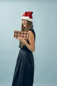 Menina com uma caixa de presente nas mãos e um chapéu de papai noel