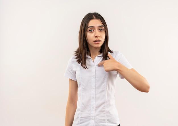 Menina com uma camisa branca apontando para ela mesma parecendo confusa em pé sobre uma parede branca