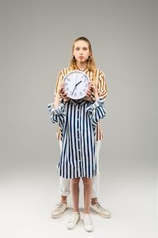 Menina com uma camisa listrada grande fechando o rosto com o relógio redondo enquanto uma amiga alta está atrás