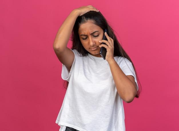 Menina com uma camiseta branca parecendo confusa e muito ansiosa enquanto fala no celular em pé sobre um fundo rosa